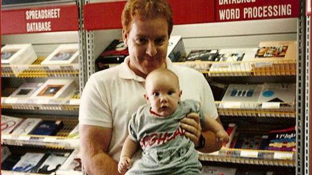 A baby sits on his dads lap in a hardware store