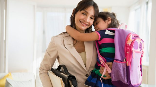 A woman is holding her briefcase in one hand and in the other she is holding her daughter