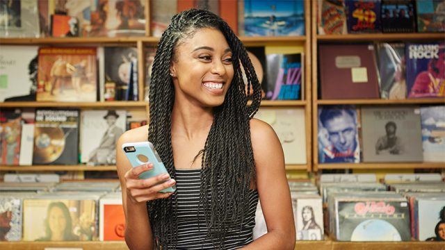 A woman is smiling while she holds her cellphone; she is in a record store