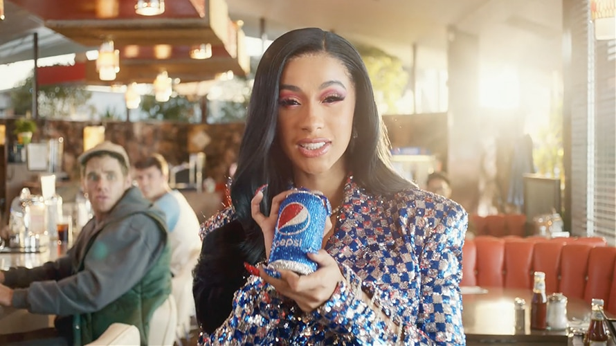 Cardi B holding a can of Pepsi in a restaurant for a super bowl advertisement
