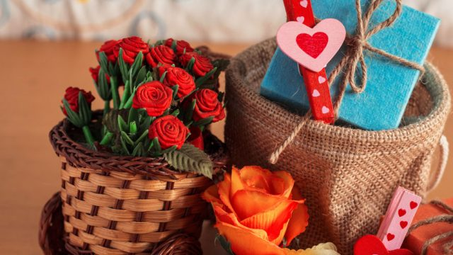 A gift basket; there is a basket of roses; a basket with a present wrapped in blue paper; as well as an orange flower