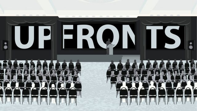 Many of people sit in an auditorium; at the front is a person speaking to the crowd; behind the speaker a banner says UPFRONTS