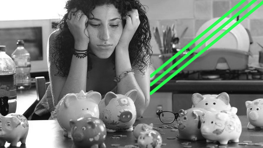 A woman sits hunched over, looking upset, and staring at piggy banks.