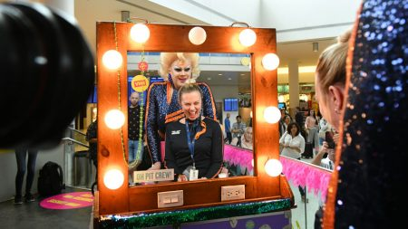 Drag queen and flight attendant in front of a makeup mirror