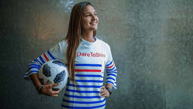 """Female Soccer star poses with a soccer ball in a red, white, and blue striped shirt that says """"Dare to Shine"""""""