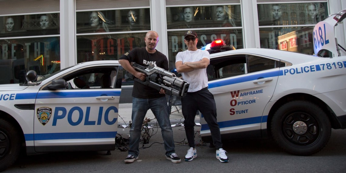 Michael Krivicka and Chris Yoon of WhoIsTheBaldGuy agency hold a video game gun model and stand in front of a broken prop police car for the Warframe Opticor Stunt.