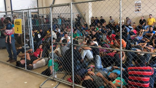 Crowd of people fenced in at the U.S. Border Control Station in McAllen, Texas.