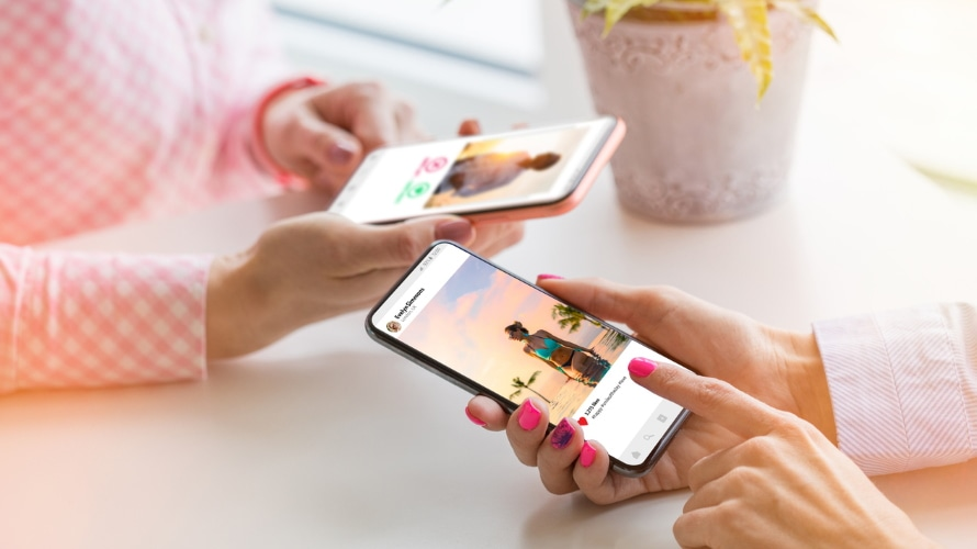 two women holding mobile phones and looking at photos