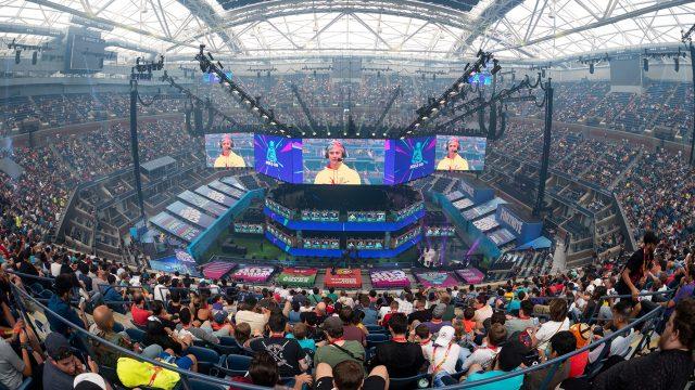 Man on a huge flatscreen onstage addressing a crowd.