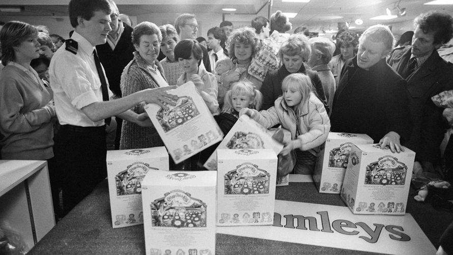 People grab packages of Cabbage Patch Kids.