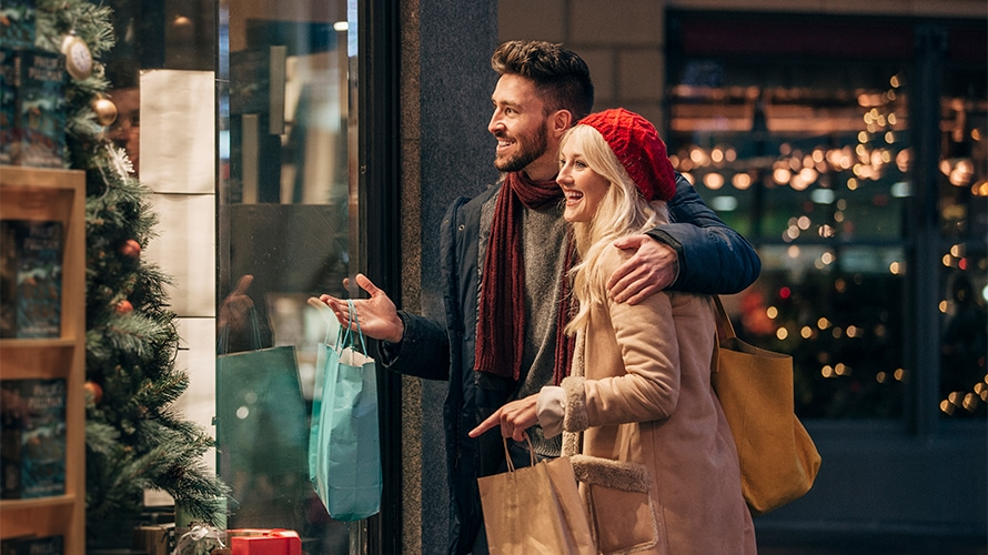 young couple window shopping during the holidays