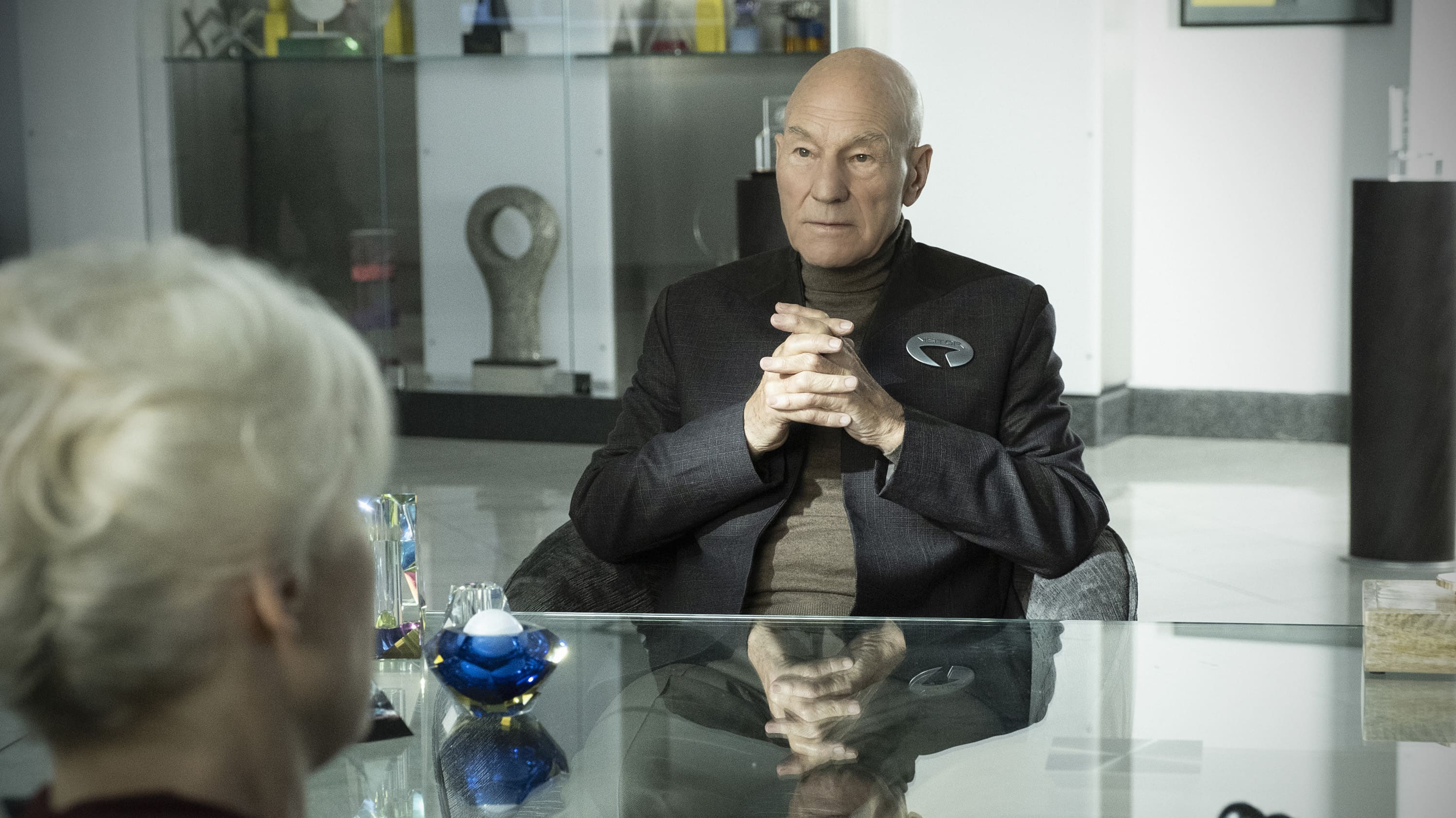 Patrick Stewart from Star Trek sitting at a glass table with his hands clasped.