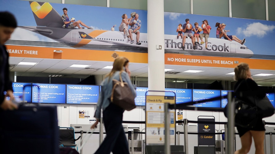 A traveler walks past Thomas Cook signage in an airport.