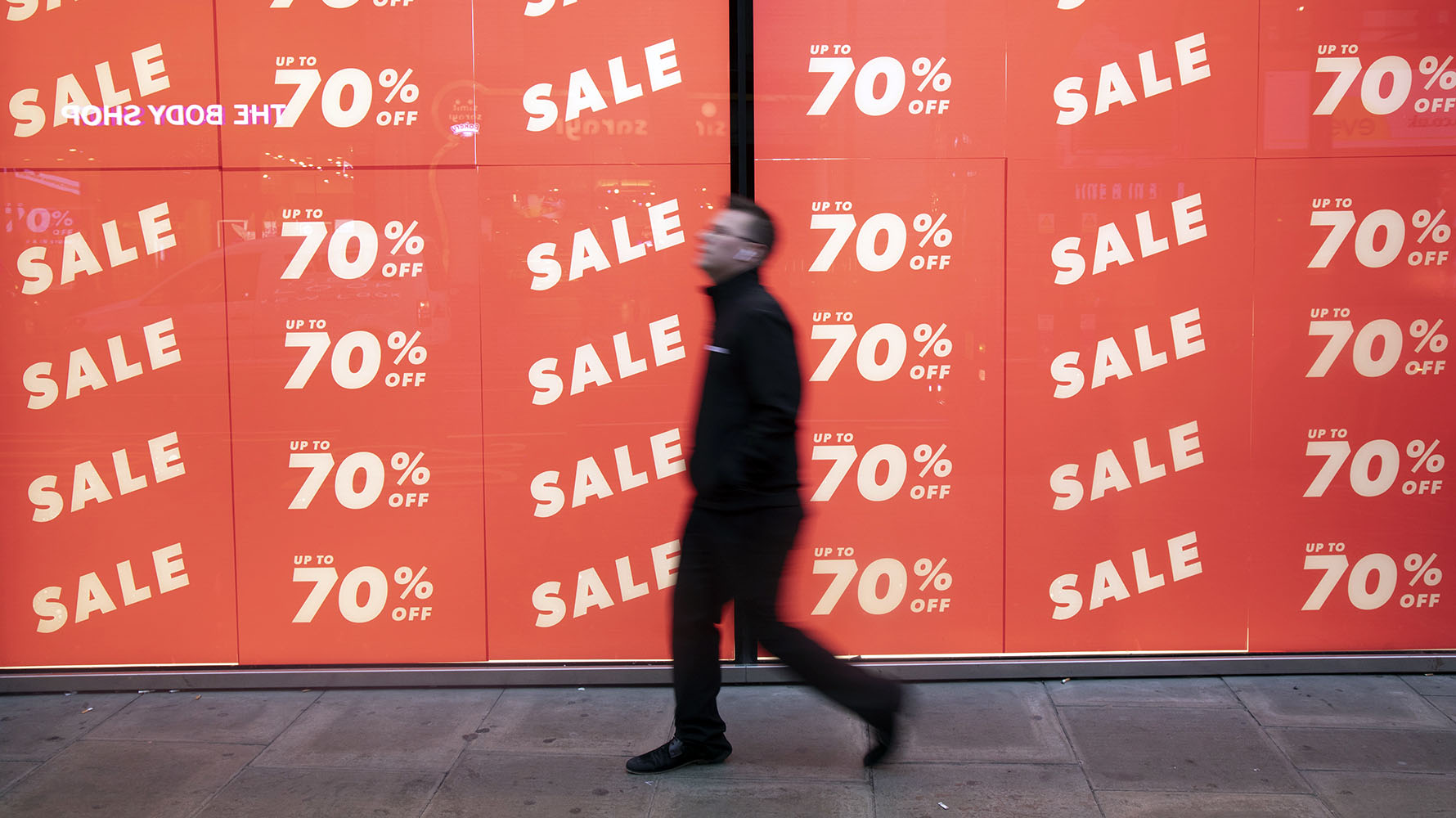 People out shopping on Oxford Street walk past large scale January sale signs in red and white for major high street clothing retail shops on 7th January 2019 in London, United Kingdom. Its time for the Winter sales, and most shops are advertising big reductions in prices. Bargains are available and the shopping streets are busy. Oxford Street is a major road in the West End of London. It is Europe