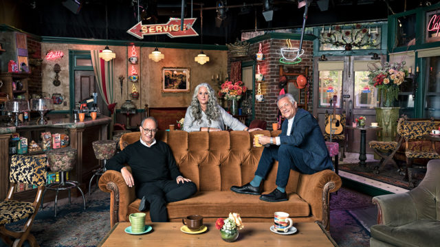 Friends creators David Crane, Marta Kauffman and Kevin Bright gather around the orange couch from Central Perk at the NYC pop-up museum.