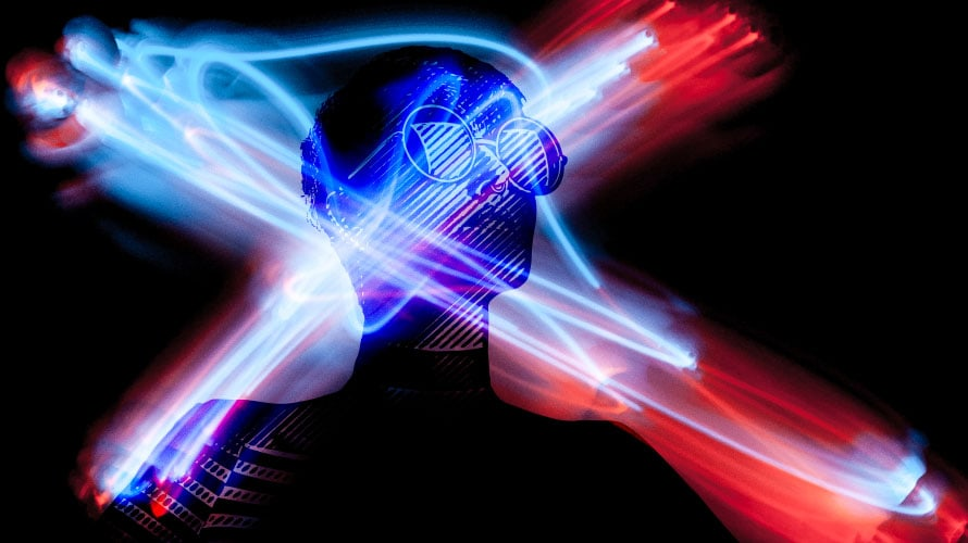A person in glasses in the shadows with an X of laser lights crossing over their face.