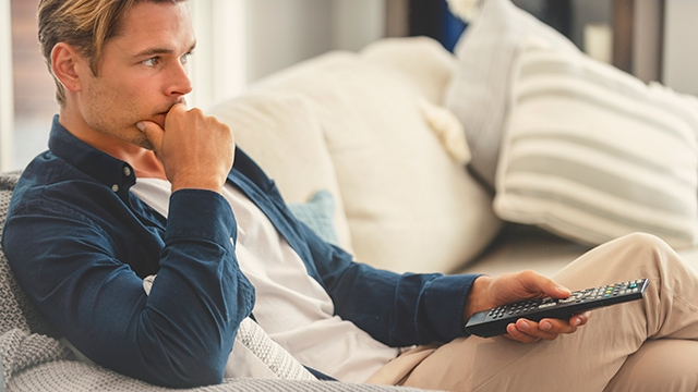 White man sitting on a sofa holding a television remote control with a pensive look on his face