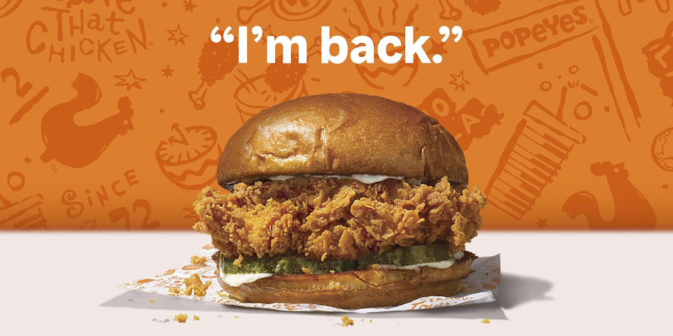 The Popeyes Chicken Sandwich sits on a wrapper under the words I