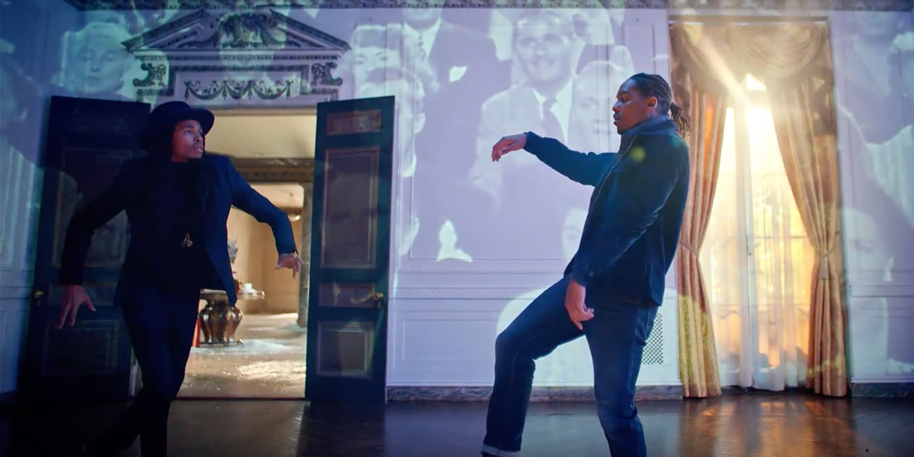Two men dancing indoors with image projections on the wall