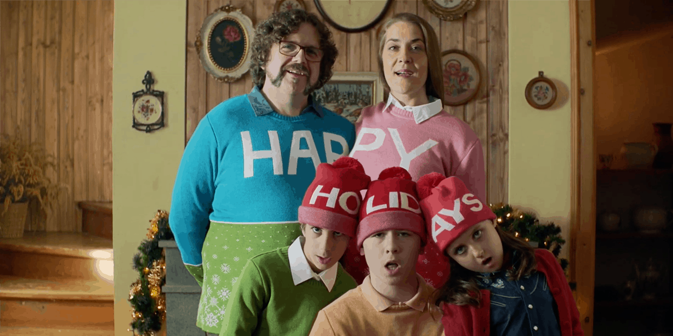 a family in christmas sweaters and hats singing