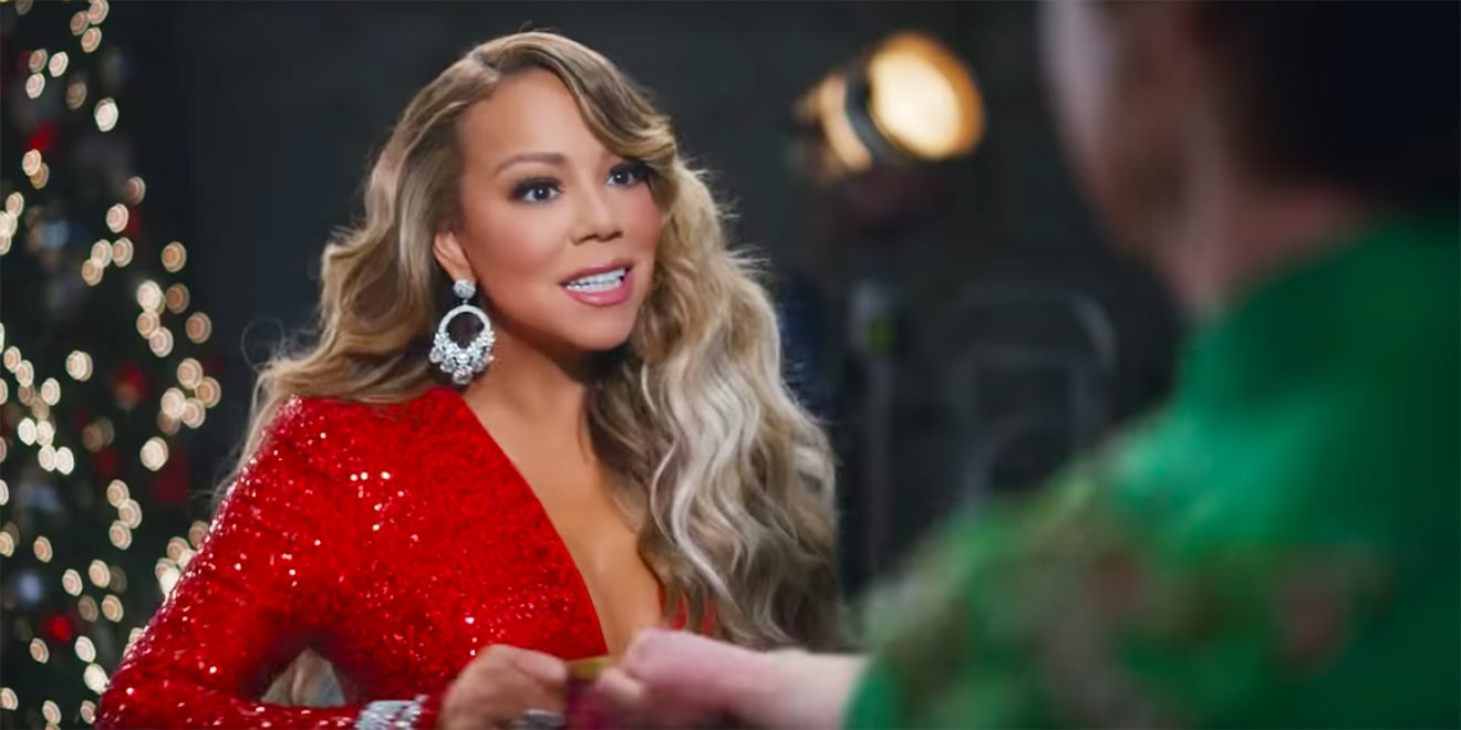 Mariah Carey holds a bag of chips with determination while a man in green holds the same chips