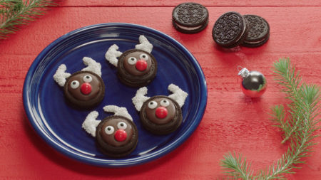 Reindeer oreo cookies on a blue plate with 3 oreos on the red table