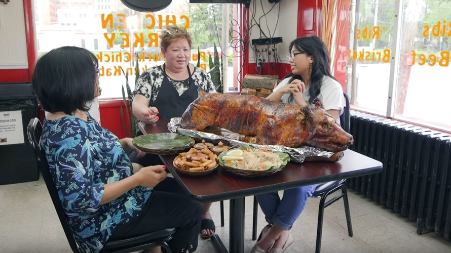 three women sit around a table with lechon and other food
