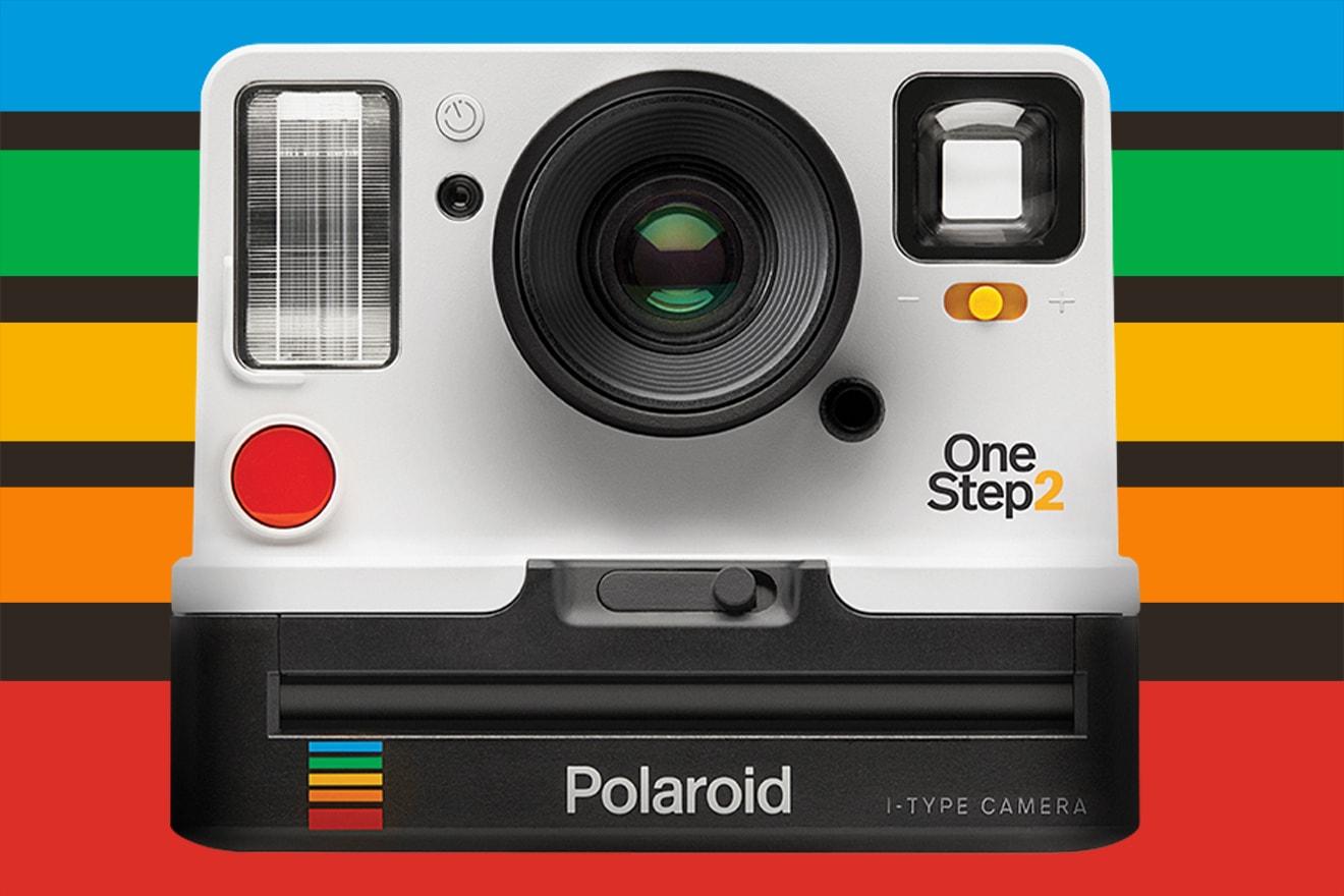 a polaroid camera on a rainbow background