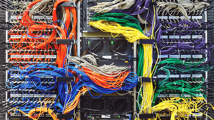 computer servers nearly obscured by bundles of wires