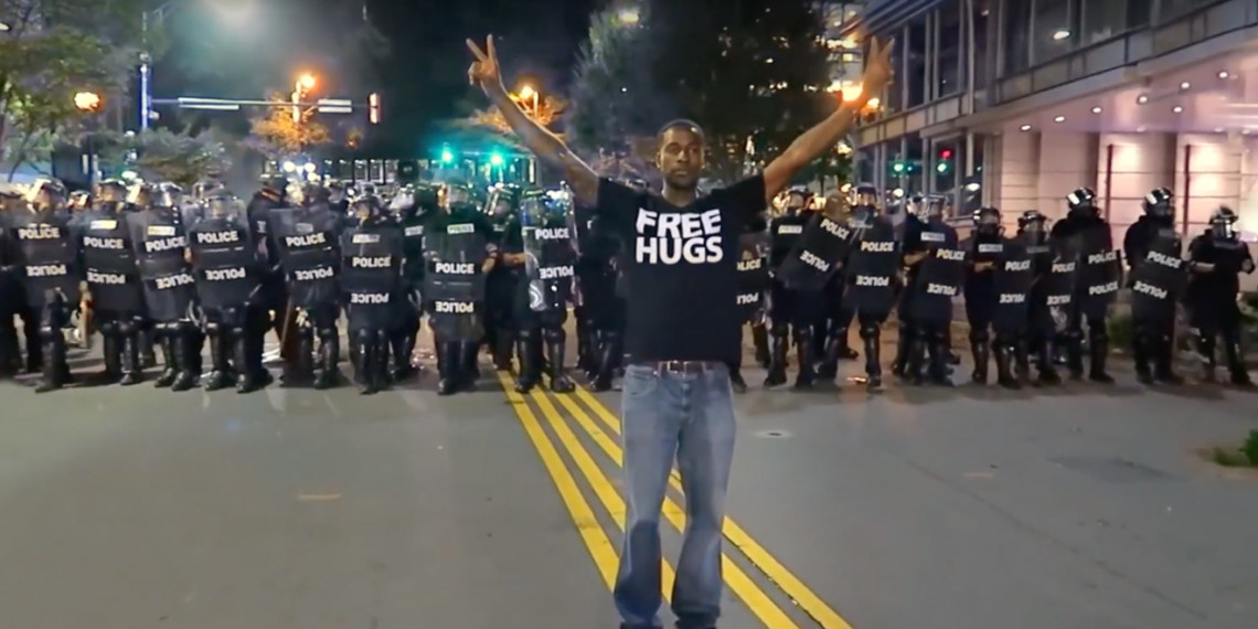 "Man standing in front of a police blockade holding the peace signs with a ""free hugs"" shirt on"