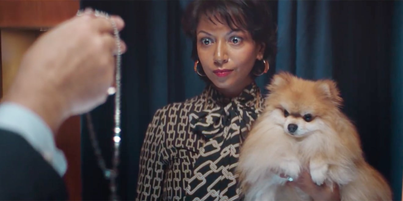 A woman with wide eyes holding a dog and looking at a man's hand holding a piece of jewelry