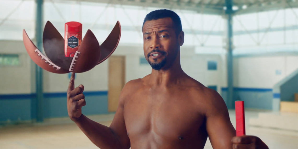 Isaiah Mustafa using his index finger to hold up a football that