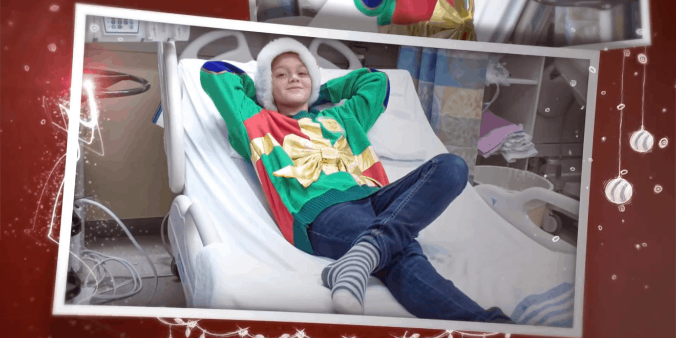 a kid laying in a hospital bed with an ugly christmas seater on