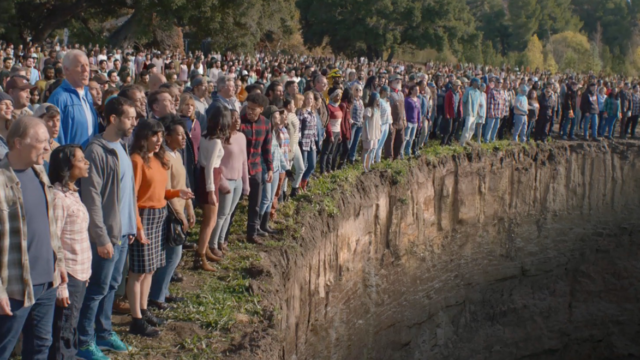 people standing at the edge of a giant hole