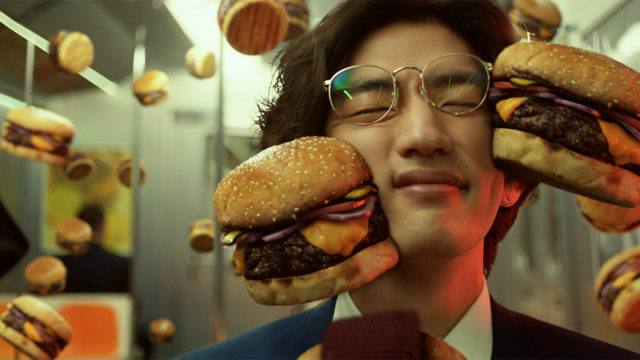 Burgers collide with a subway rider's face in an ad for Postmates