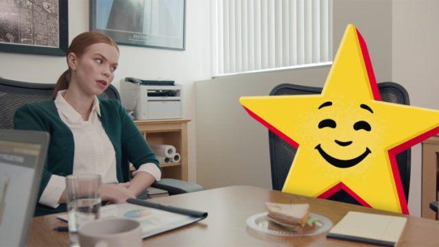 A woman talking to a talking star in a Carls Jr. ad