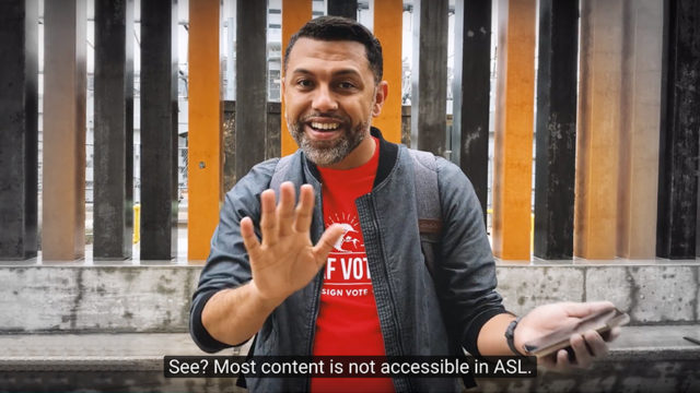 "A man with a beard and dark hair, wearing a red t-shirt and light jacket, stands on the street speaking ASL. The caption reads: ""see? Most content is not accessible in ASL."""