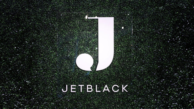 White Jetblack logo on greenish-black background