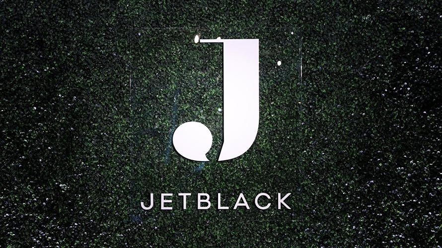White Jetblack logo on greenish-black background