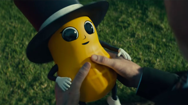 A baby version of Mr. Peanut looks up at someone holding him