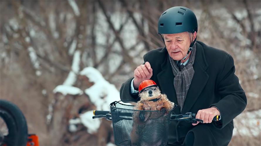Bill Murray wears a bike helmet and rides a bike with a helmet-wearing groundhog in the basket