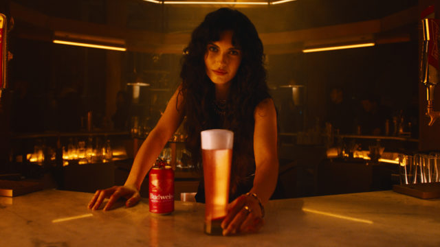woman holding a glass of Budweiser Nitro Gold behind bar