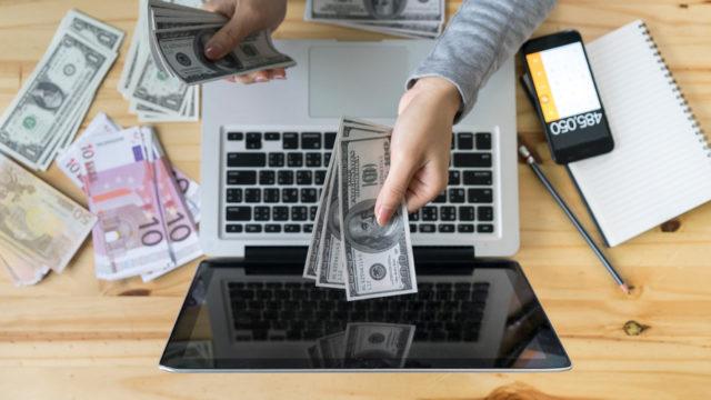 a person handing money to a computer screen