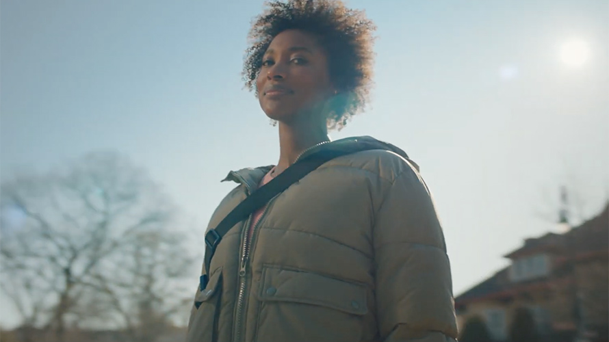 Black woman wearing a winter coat stares downward at camera with knowing smile on her face