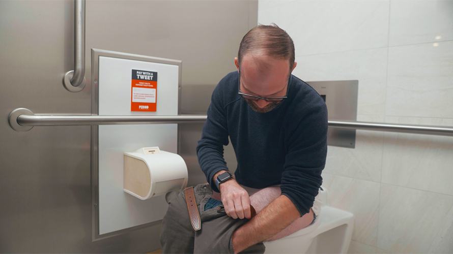 A man on a toilet fumbles for change in his pocket to pay a coin-operated toilet paper dispenser