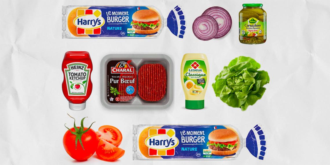 An overlay of hamburger buns, ketchup, onions, pickles, ketchup, beef, mayonnaise, tomatoes and more buns