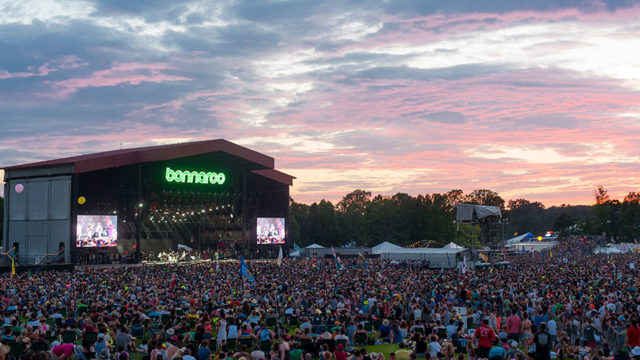 a concert at sunset with a crowded stage that says bonnaroo