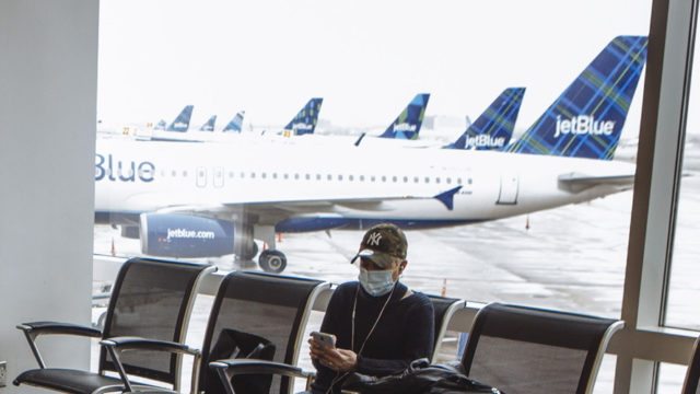 a man in a mask waiting at an airport
