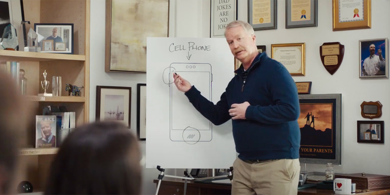 A man pointing to a drawing of a smartphone