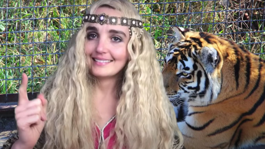 Chloe Fineman dressed as Carole Baskin with a photo of a tiger behind her